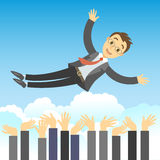 Successful businessman being throwing in the air by his teamwork Stock Image