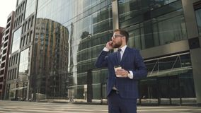 Successful businessman in blue suit holding coffee cup and having phone talk outside stock video footage