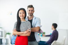 Successful businessman and businesswoman standing with crossed a. Rms and their team on background in the office Stock Photography