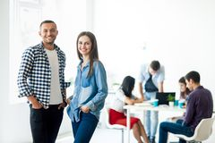 Successful businessman and businesswoman standing in the office. With their team on background Stock Image