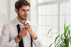 Successful businessman buttoning shirt before going out Royalty Free Stock Photos