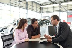 Successful businessman in a car dealership - sale of vehicles to. Customers stock images