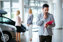 Successful businessman in a car dealership - sale of vehicles to customers stock photos