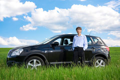 Successful businessman with car on grassland. Successful businessman with car on green grassland under blue sky stock photos