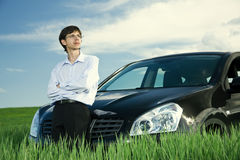 Successful businessman with car on grassland. Successful businessman with car on green grassland under blue sky royalty free stock images