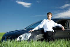 Successful businessman with car on grassland. Successful businessman with car on green grassland under blue sky royalty free stock photos
