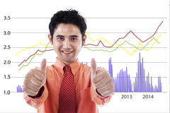 Successful businessman with chart. Happy businessman giving thumbs up in front of business graph Royalty Free Stock Photography