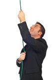 Successful businessman climbing rope Stock Photo