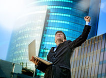 Successful businessman with computer laptop happy doing victory celebrating success Stock Photography