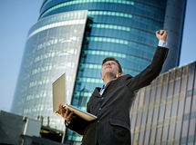 Successful businessman with computer laptop happy doing victory sign Royalty Free Stock Images