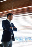 Successful businessman with crossed arms thinking about something while standing near window with a venetian blinds Stock Photography