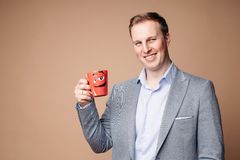 Successful businessman with cup with reassuring slogan. Studio portrait of determined successful businessman in suit and shirt holding red mug with positive stock photography