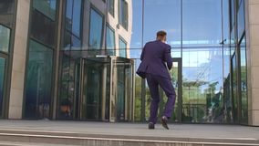 Successful businessman dancing near the building.