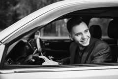 Black and white art monochrome photography. Successful businessman in a dark business suit with a red in the car. Stylish man. Young driver Stock Image