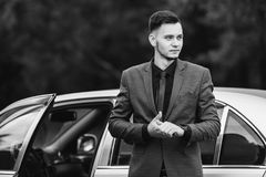 Black and white art monochrome photography. Successful businessman in a dark business suit with a tie on the background of a gray car. Stylish man Stock Photos