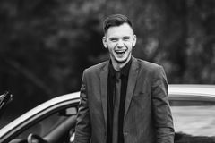Black and white art monochrome photography. Successful businessman in a dark business suit with tie on the background of a gray car. Stylish man Stock Photo