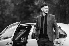 Black and white art monochrome photography. Successful businessman in a dark business suit with tie on the background of a gray car. Stylish man Royalty Free Stock Photography
