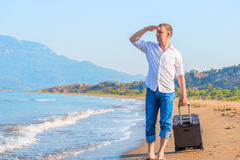 Successful businessman on a desert island. With a suitcase stock photography
