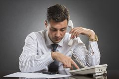 Successful businessman dialing on phone. Successful businessman in white shirt with necktie picking up the receiver and dialing a phone number while sitting at Stock Image