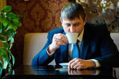 Successful businessman, director, businessman in a business suit in a cafe at lunch drinking a cup of coffee. Lunch, coffee time.  royalty free stock photos