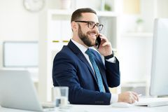 Successful businessman discussing contract on phone. Positive successful young bearded businessman in eyeglasses and suit sitting at desk and discussing contract stock image