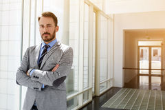Successful businessman dressed in expensive suit is standing in hallway his company near copy space for your advertising text mess stock image