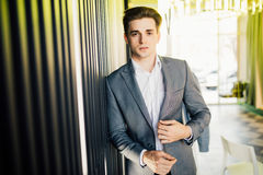 Successful businessman dressed in expensive suit is standing in hallway his company. Young male manager is posing in modern office. Successful businessman royalty free stock photography