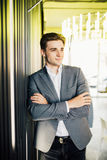 Successful businessman dressed in expensive suit is standing in hallway his company. Young male manager is posing in modern office. Successful businessman stock images