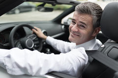 Successful businessman driving his car. Successful confident businessman driving to work with his brand new expensive car, he is smiling at camera royalty free stock photography