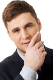 Successful businessman with finger under chin. Stock Photo
