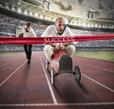 Successful businessman on the finishing line. Businessman drives a toy car beyond the red ribbon at the arrival of a race while a men runs at a disadvantage Royalty Free Stock Images