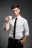 Successful businessman in formalwear holding cup of coffee while standing Stock Photo