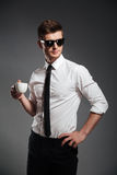 Successful businessman in formalwear holding cup of coffee while standing Stock Images