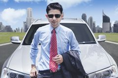 Successful businessman in front of luxury car. Portrait of successful businessman in front of luxury car with cityscape background Royalty Free Stock Images