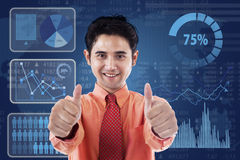 Successful businessman with futuristic interface. Happy businessman giving thumbs up in front of business graph Royalty Free Stock Photo