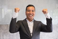 Successful businessman gesturing with happiness and gladness at. Successful asian businessman gesturing with happiness and gladness at office. Start up stock photography