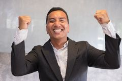 Successful businessman gesturing with happiness and gladness at. Successful asian businessman gesturing with happiness and gladness at office. Start up royalty free stock images