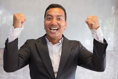 Successful businessman gesturing with happiness and gladness at. Successful asian businessman gesturing with happiness and gladness at office. Start up royalty free stock photography