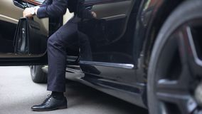 Successful businessman getting out of premium class car, arrival to workplace stock footage