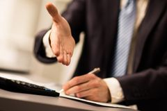 Successful businessman giving a hand Stock Photo