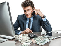 Successful businessman going to make a call by cell phone. While working with PC computer and calculator royalty free stock photos