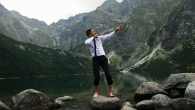 Successful businessman happy from the victory, crazy happy emotions and dancing near a lake in the mountains at sunset. Successful confident businessman happy stock video