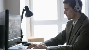 Successful businessman in headphones sitting at his desk, working on a computer by the panoramic Window. Successful businessman sitting at his desk, working on stock photos
