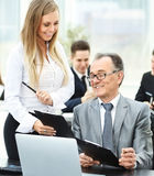 Successful businessman and his aides discussed the work plan on the background of working business team Stock Photos