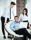 Successful businessman with his assistants in a discussion of the information from the laptop. Office life royalty free stock images