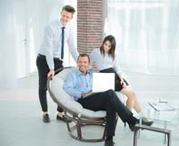 Successful businessman with his assistants in a discussion of the information from the laptop. Office life royalty free stock image