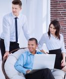 Successful businessman with his assistants in a discussion of the information from the laptop. Office life stock photo