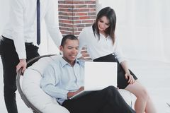 Successful businessman with his assistants in a discussion of the information from the laptop. Office life stock photography