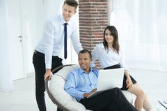 Successful businessman with his assistants in a discussion of the information from the laptop. Office life royalty free stock photos