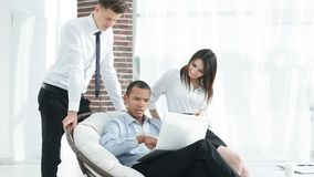 Successful businessman with his assistants in a discussion of the information from the laptop. Office life stock images